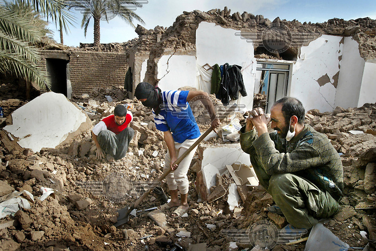 Surviving members of a family who lost their mother and two sons in the Bam earthquake search the ruins of their home..An earthquake measuring 6.3 on the Richter scale caused widespread devastation in the ancient city of Bam and other parts of Kerman Province, leaving at least 30,000 people dead.