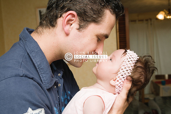 Polish father rubbing noses with baby daughter,