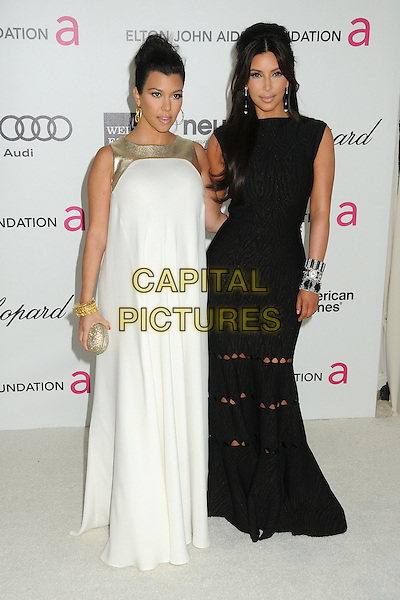 Kourtney Kardashian, Kim Kardashian.20th Annual Elton John Academy Awards Viewing Party held at West Hollywood Park, West Hollywood, California, USA..February 26th, 2012.oscars black white dress sisters gold trim sleeveless clutch bag full length .CAP/ADM/BP.©Byron Purvis/AdMedia/Capital Pictures.
