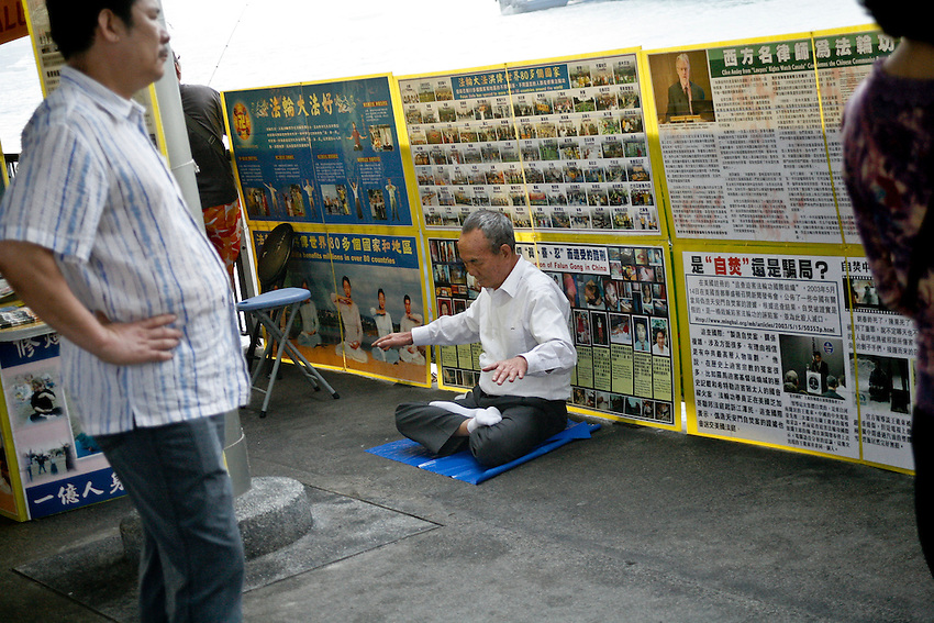 A member of the Falungong movment practicing meditation in public on the pier of Tsimshatsui, near Kowloon. Hong-kong.
