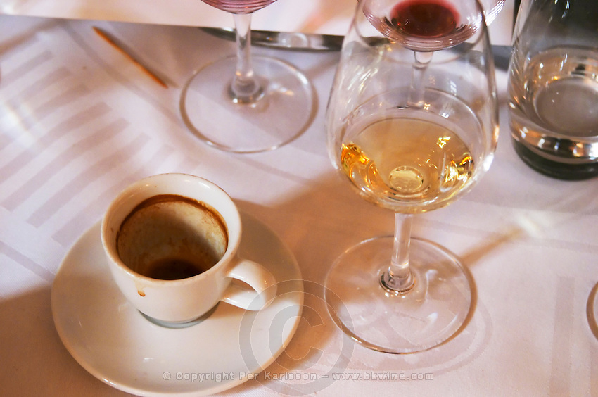 After a luxurious lunch dinner: Empty wine glasses and a finished cup of coffee on a linen table cloth at the gastronomic restaurant Maceo in Paris