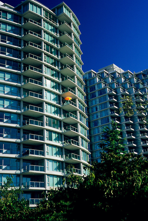 Umbrella on balcony, condominium tower at Coal Harbor in West End of Vancouver taken from seawall in summer.