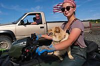 Johnna Bouker, from Dillingham, Alaska, rides a four-wheeler with her dog as her father, John Paul Bouker, looks on, in Ekuk, Alaska on July 4, 2019. Booker has worked on her family's setnet site of (Photo by Karen Ducey)