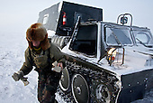 """Andrei exits his snow tank to deliver light bulbs to colleagues in the colony set up by oil and gas prospecting company """"Siesmorevzedka"""" in the Arctic tundra. Typically, they work in the cold, isolated Arctic tundra for the entire winter, returning to civilisation only in spring."""