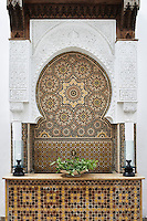 A decorative Moorish mosaic tiled panel is set behind a table in the outside courtyard