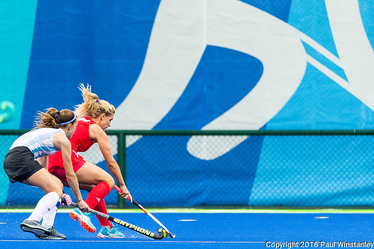 Georgie Twigg #7 of Great Britain protects the ball against Carla Rebecchi #11 of Argentina during Argentina vs Great Britain in women's Pool B game  at the Rio 2016 Olympics at the Olympic Hockey Centre in Rio de Janeiro, Brazil.
