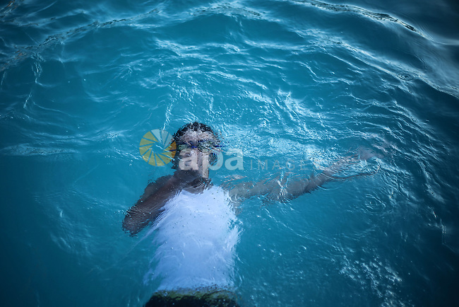 A picture taken on August 10, 2013 shows A Palestinian boy swimming at a pool in Gaza City. Photo by Mahmoud Hamda