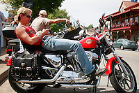 "NWA Democrat-Gazette/DAN HOLTMEYER<br /> Derrick Catalini of Fort Smith lounges on his Harley Davidson Sportster on Dickson Street in Fayetteville as crowds flow past. This is his first year at Bikes, Blues & BBQ, and the Florida native said so far it seems like it has better vendors, better turnout and a better surrounding community than other bike events he's been to. ""It's pretty awesome,"" he said. ""This is a good rally."""