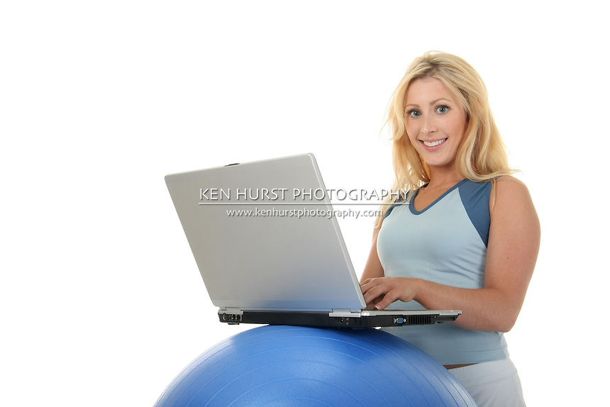 Attractive young blonde woman using an exercise ball as a desk for her laptop computer.