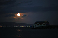 The harvest fool moon rises over Mumbles boathouse near Swansea, Wales, UK.