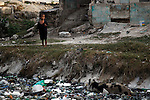 World Water Day. A child is looking a pig near  a little river which goes through Cite Soleil, a neighborhood of Port au Prince, Haiti