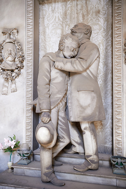 Picture and image of the stone sculpture of a grieving father and son standing at the doors of a tomb. Piccollo Tomb sculpted by G Moreno 1891. Section A, no 26, The monumental tombs of the Staglieno Monumental Cemetery, Genoa, Italy