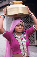 INDIA Dhar, Adivasi woman carry brass pot with water on the head / INDIEN Dhar Adivasi Frau traegt Trinkwasser in einem Messing Krug auf dem Kopf
