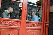 Two men talk in a pub window in the City of London.