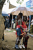 Lolgorian, Kenya. Two Maasai moran with umbrella outside shops in the town.