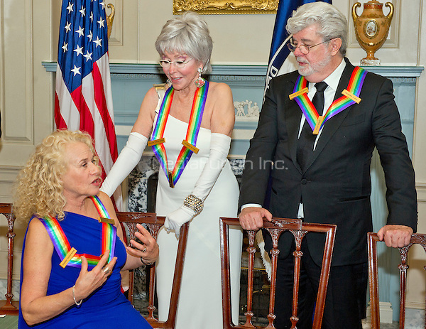 Singer-songwriter Carole King, left, actress and singer Rita Moreno, center, and filmmaker George Lucas, three of the five recipients of the 38th Annual Kennedy Center Honors share a conversation prior to posing for a group photo following a dinner hosted by United States Secretary of State John F. Kerry in their honor at the U.S. Department of State in Washington, D.C. on Saturday, December 5, 2015.  The 2015 honorees are: singer-songwriter Carole King, filmmaker George Lucas, actress and singer Rita Moreno, conductor Seiji Ozawa, and actress and Broadway star Cicely Tyson.<br /> Credit: Ron Sachs / Pool via CNP/MediaPunch