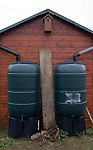 Two water butts illustrating concept of watershed dividing drainage basins on roof