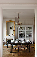 The dining room is simple and elegant with a 19th century gilt-framed mirror above the fireplace, a black lacquered dining table and chairs and a white-painted glass-fronted china cabinet