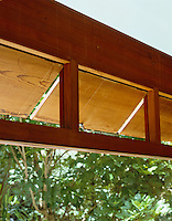 A row of wooden shutters runs along the top of the picture windows allowing air to circulate throughout the house
