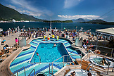 USA, Alaska, Ketchikan, passengers lay by the pool as the cruise ship departs Ketchikan through the Clarence Straight for Juneau