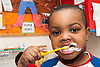 Young child at a day nursery brushing his teeth UK