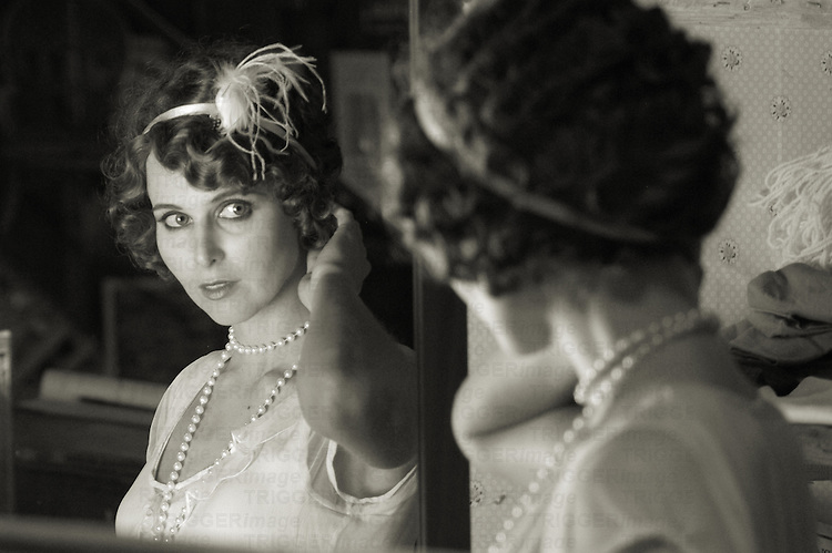 Woman dressed as flapper looking into the mirror