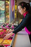 FRANCE, Paris, a young shop woman, arranging Patisseries in Maison Fauchon