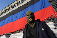A hooded Pro Russian activist stands in front of the Flag of the Donetsk People Republic in the the city hall. Slavyansk city. Donetsk region.