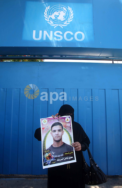 A Palestinian woman holds pictures of Palestinian prisoners Mahmoud Al-Sarsak and Akram Al-Rikhawi, whose are still refusing food for 86 days after a deal was made to end a mass prisoner hunger strike, during a demonstration in their support, in front of the UNRWA headquarters in the Gaza city on 12 June, 2012. Photo by Ashraf Amra