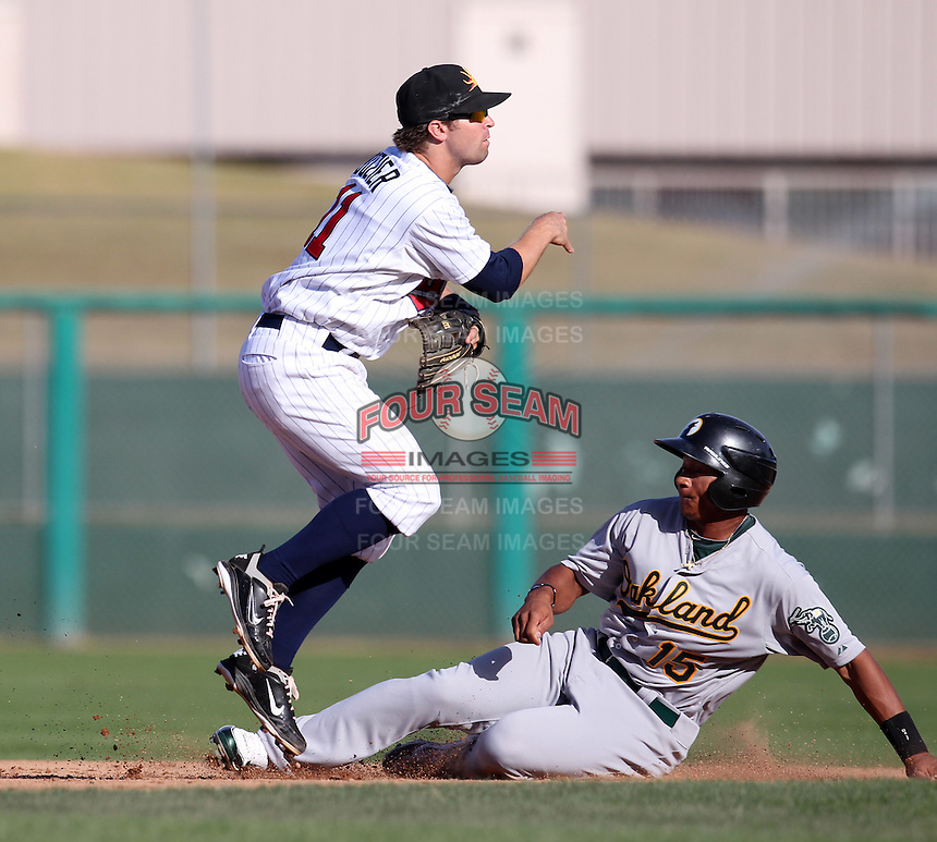 Mesa Solar Sox second baseman Brian Dozier #11 turns a double play as Michael Choice #15 slides in during an Arizona Fall League game against the Phoenix Desert Dogs at HoHoKam Park on November 3, 2011 in Mesa, Arizona.  Mesa defeated Phoenix 8-7.  (Mike Janes/Four Seam Images)
