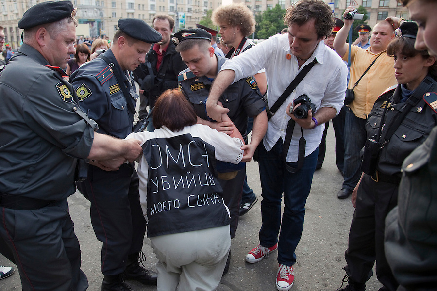 """Moscow, Russia, 31/05/2010..A demonstrator wearing a banner saying """"The OMON murdered my son"""" collapses after being arrested by OMON riot police as they break up an opposition protest in central Moscow and arrest around 170 people. Opposition activists hold regular demonstrations on the 31st day of the month, protesting against restrictions on the freedom of assembly, which is protected by article number 31 of the Russian constitution."""