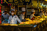 Cooking street food (including barbecue), the Old Town (Dayan) of Lijiang, Yunnan Province, China. The Old Town is a UNESCO World Heritage Site.