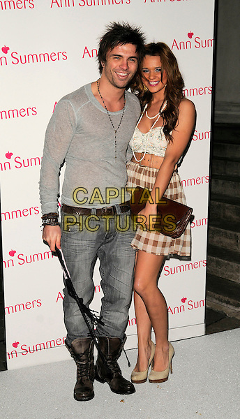 DALE HOWARD & NAOMI MILLBANK SMITH.The Ann Summers Enchantment Collection launch party, The Baccarat Room, 1 Marylebone Rd., London, England..December 1st, 2008.anne full length Millbank-Smith clutch bag beige belt waist brown plaid skirt cream white camisole top grey gray jeans denim whip boots jumper platform shoes.CAP/CAN.©Can Nguyen/Capital Pictures.
