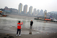 CHINA. Sichuan Province. Chongqing. Tourists next to The Yangtze River which is at its lowest level in 150 years as a result of a country-wide drought. Chongqing is a city of over 3,000,000 people, famed for being the capital of China between 1938 and 1946 during World War II. It is situated on the banks of the Yangtze river, China's longest river and the third longest in the world. Originating in Tibet, the river flows for 3,964 miles (6,380km) through central China into the East China Sea at Shanghai.  2008.