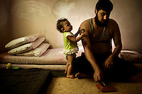 27 year old Jalal Ahmed Aziza with his son and daughter they live with his pregnant wife in a 10m2 room in at the Cyber City Refugee Camp. This former electronics factory has been turned into a refugee camp for displaced Syrians, mostly of Palestinian origin. The six floor building is home to about 500 refugees. They are from Dera in Syria but have been living here for 2 years. He says that he was imprisoned for 60 days, for supporting the revolution, until his father managed to get him out by paying 5000 USD, after that he fled to Jordan and ended up here. He says he hates the place and despite the obvious danger he talks about going back to Syria to fight with the FSA. Approximately two million people have fled the conflict in Syria since it began in 2011, with nearly half a million in Jordan.