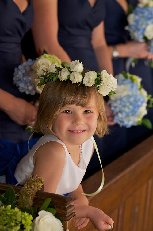 Closeup of smiling flower girl in church wearing crown of white roses.