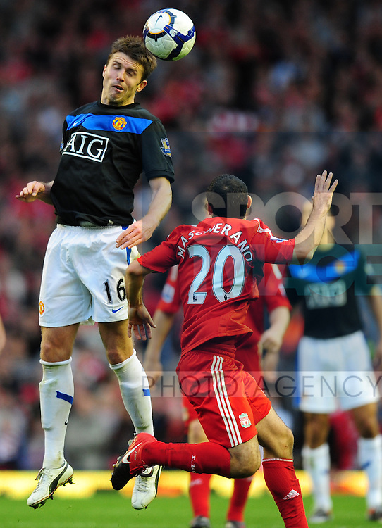 Michael Carrick of Manchester United rises above Javier Mascherano of Liverpool