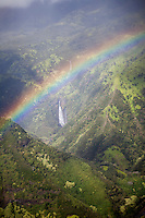 A rainbow is seen about a waterfall during a helicopter tour around the island of Kauai, HI.