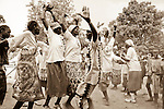 """In Rumbek, South Sudan, Dinka men and women hold their arms up high to symoblize cow horns while jumping in this traditional """"jumping dance."""""""