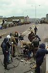 Riots rioting youths digging up the road to make missiles to throw at the British army.  Belfast Northern Ireland Uk 1980s