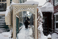 A man walks in between buildings in Harvard Square in Cambridge, Massachusetts, USA, on Saturday, Feb. 9, 2013, after Winter Storm Nemo hit the area.
