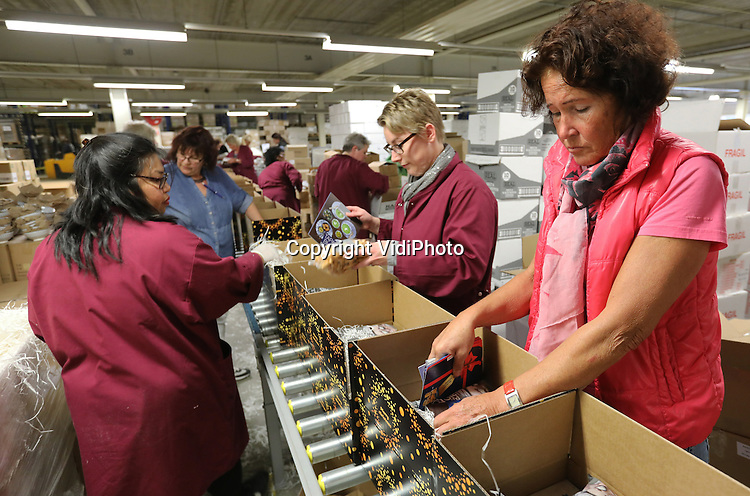 Foto: VidiPhoto<br /> <br /> DUIVEN - Duizenden kerstpakketten rollen dinsdag over de lopende band. Bij Makro Kerstpakketten in Duiven, de grootste inpakcentrale van Nederland, is begonnen met de verwerking van de eerste serie van de in totaal ruim 1,4 miljoen kerstpakketten die bij het bedrijf worden geproduceerd. En dan zijn niet alle orders al binnen. Wat nu ingepakt wordt zijn standaard pakketten. Het kerstpakket in Nederland blijft ongekend populair, vertelt marketing manager Lidushka Ruegebrink. Trends dit jaar zijn cadeauboxen en het extra leuk verpakken van de spulletjes in het kerstpakket. Het geven van een kerstpakket door werkgevers aan werknemers blijft de belangrijkste wijze van 'waarderen' aan het eind van het jaar. Volgens onderzoek van Makro Kerstpaketten zelf blijkt dat 94 procent van de werknemers graag een eindejaarsgeschenk ontvangen. Tijdens de topdrukte, eind oktober, zijn er 500 mensen bezig met het inpakken van de kerstpakketten.