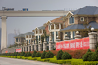 Western-style newly built modern river front housing development by railway bridge in Yichang, China