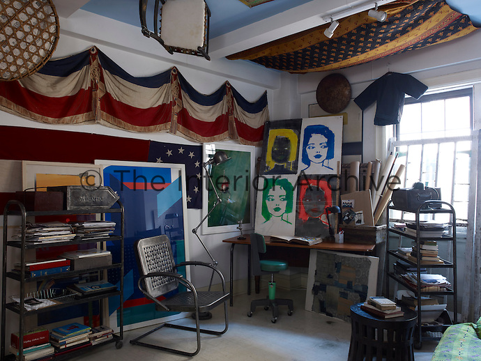 The study is furnished with a French banner and an Anglo-Indian cotton quilt hanging from the ceiling, juxtaposed with a 1940s floor lamp and a 1950s metal spring chair, while the painting on the desk is by Linda Mason