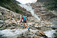 A trail runner crosses a creek while on the way to the Strahlegghorn, from Grindelwald, Switzerland.
