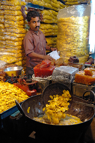 India, Kerala, Kumily. Indian man frying banana crisps to sell in Kumily (Periyar), Kerala. No releases available.