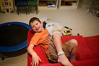"Jack Ursitii, age 7, plays on a couch during a ""sensory break"" in his home in Dover, Mass., on Monday, July 25, 2011.  Jack has been diagnosed with autism.  After school at his home, Jack works with his teacher and a therapist to do educational and independent leisure activities. Periodically Jack takes ""sensory breaks"" to stop activity and play independently, allowing him to return to his tasks with greater concentration. During the ""sensory breaks"" Jack does a variety of things, including looking at his reflection, making faces, jumping on a small trampoline or cushions, or play with an iPad...Jack Ursitti wears a small GPS ankle bracelet at all times in case he runs off from his family or caretakers. The device will be activated if he goes missing, allowing police and other searchers to find him."