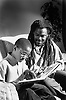Father sitting on sofa helping son to read book,