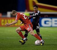 Andy Najar (14) of D.C. United fights for the ball with Ty Harden (20) of Toronto FC during the game at RFK Stadium in Washington, DC.  Toronto defeated D.C. United, 3-2.