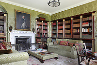 Built-in neo-classical style bookcases line the walls of the library, furnished with plush sofas and cushions
